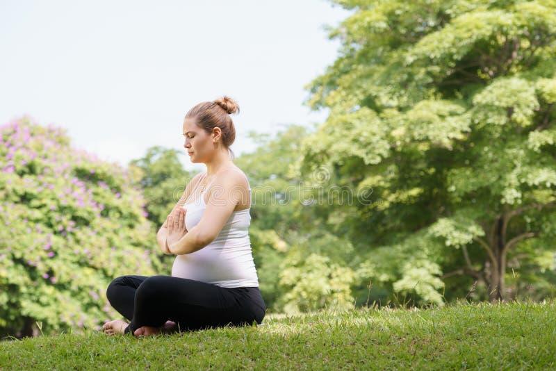 Preghiera di rilassamento di yoga del parco della pancia della madre della donna incinta immagini stock libere da diritti