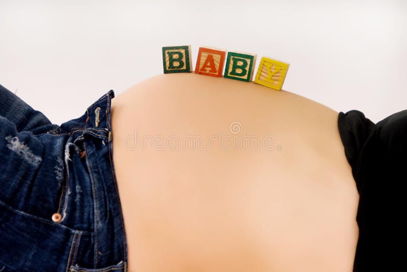 Pregnancy. A maternity portrait of a woman at nine months along in her pregnancy