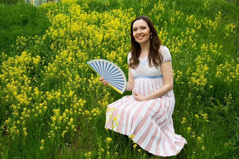 Pregnancy, motherhood, the concept of waiting-close - up of a happy pregnant woman with a big belly in a flowering meadow with a f. An, love happiness baby stock images