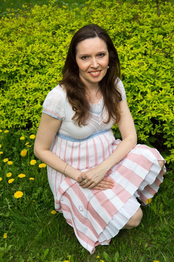 Pregnancy, motherhood, the concept of waiting-close - up of a happy pregnant woman with a big belly in a flowering meadow,. Love happiness baby royalty free stock photos