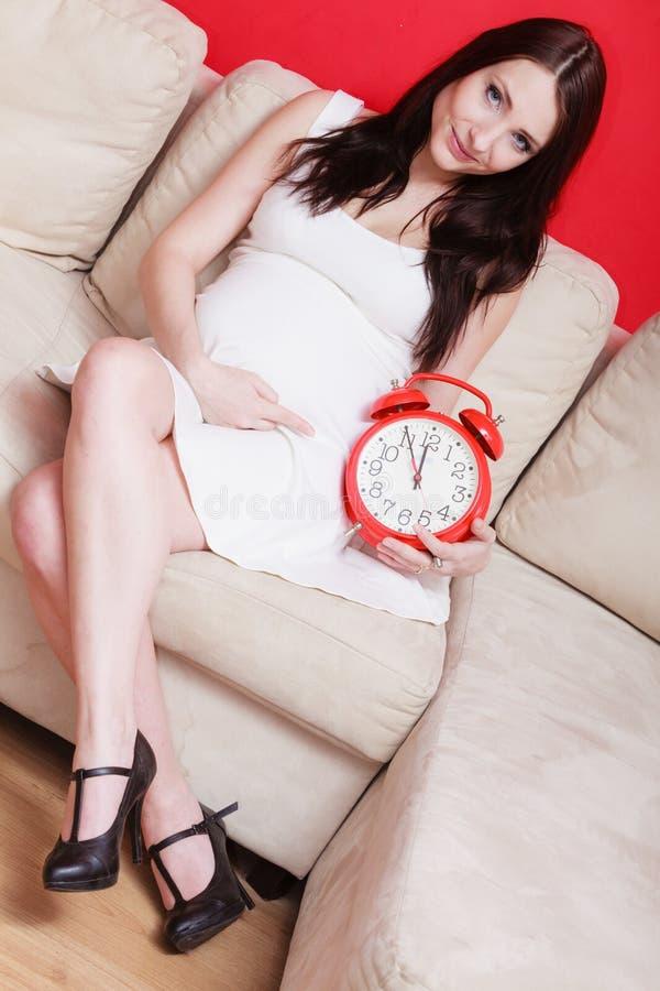 Pregnant woman sitting on sofa holding clock stock photos