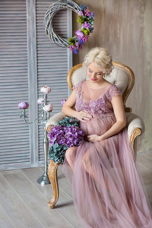 Pregnancy, motherhood and happy future mother concept - pregnant woman in airy violet dress with bouquet flowers against colorful royalty free stock images