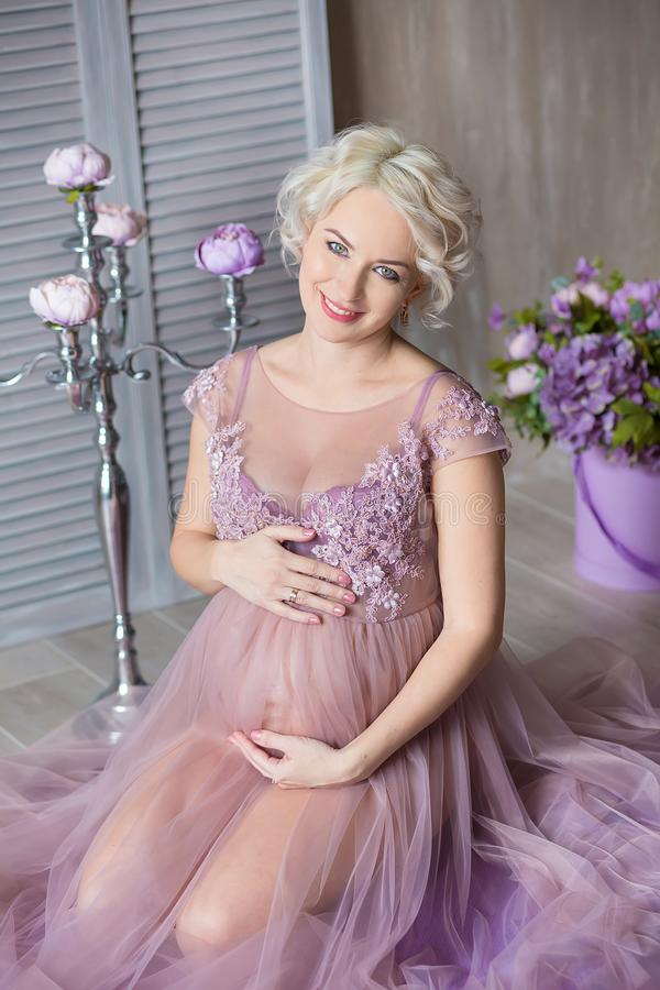 Pregnancy, motherhood and happy future mother concept - pregnant woman in airy violet dress with bouquet flowers against colorful stock images