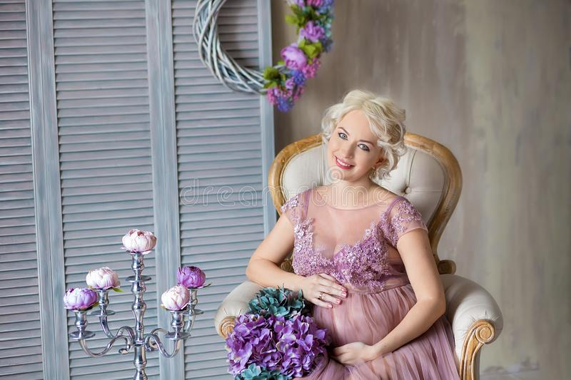 Pregnancy, motherhood and happy future mother concept - pregnant woman in airy violet dress with bouquet flowers against colorful stock photos