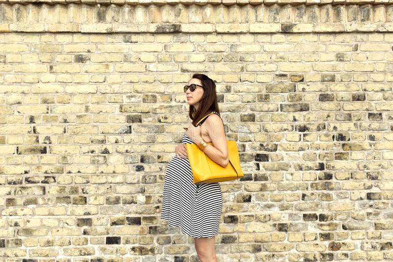 Pregnancy, motherhood and happy future mother concept - pregnant woman at city tour against brick wall.  stock photo