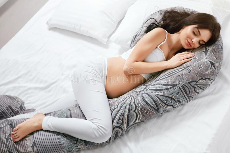Pregnancy Pillow. Pregnant Woman Resting On Body Pillow. Pregnancy Pillow. Pregnant Woman Sleeping On Body Pillow Lying On White Bed. High Resolution royalty free stock image