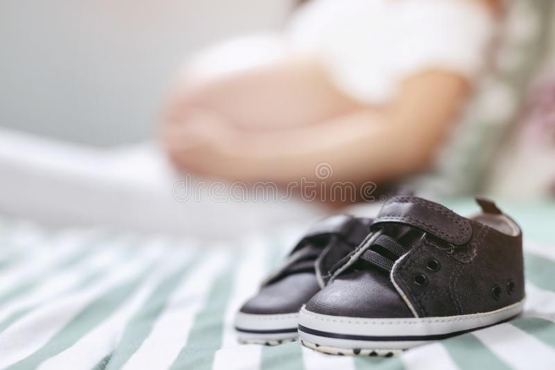 Pregnancy. a portrait of a pair of baby small shoes for the unborn near it with a pregnant woman hugging her belly with love, warm. Th relaxing at home in royalty free stock photos