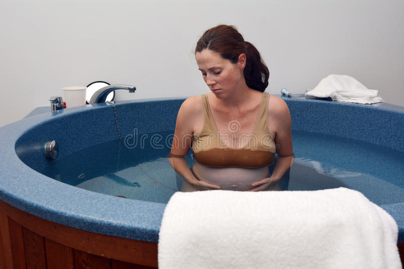 Pregnancy - pregnant woman natural water birth. Pregnant woman during natural water birth royalty free stock image