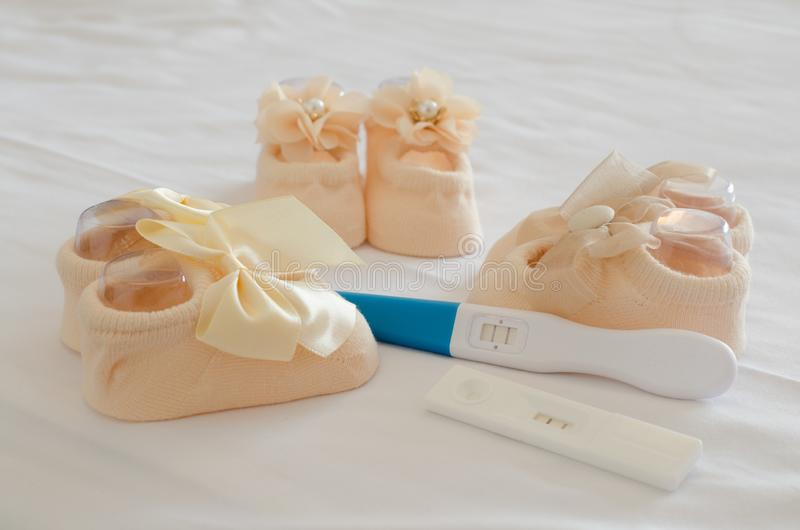 Pregnancy test and baby shoes. Ready to have children stock photos