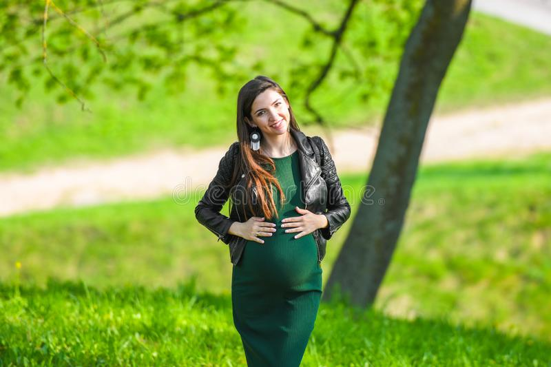 Pregnancy in warm weather. Happy pregnancy and motherhood concept. Young pregnant woman enjoying the fresh air and warm weather. Outside stock image