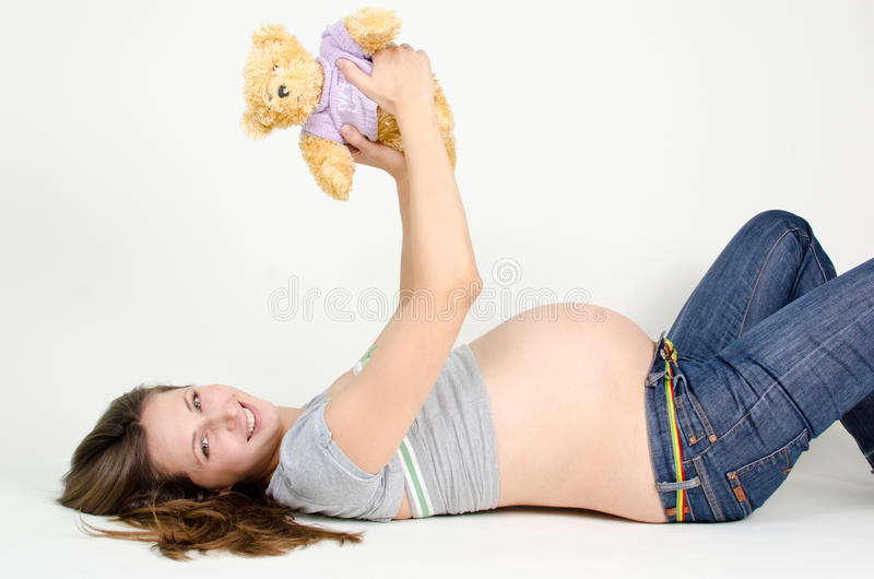 Pregnant. Woman with a teddy bear stock image