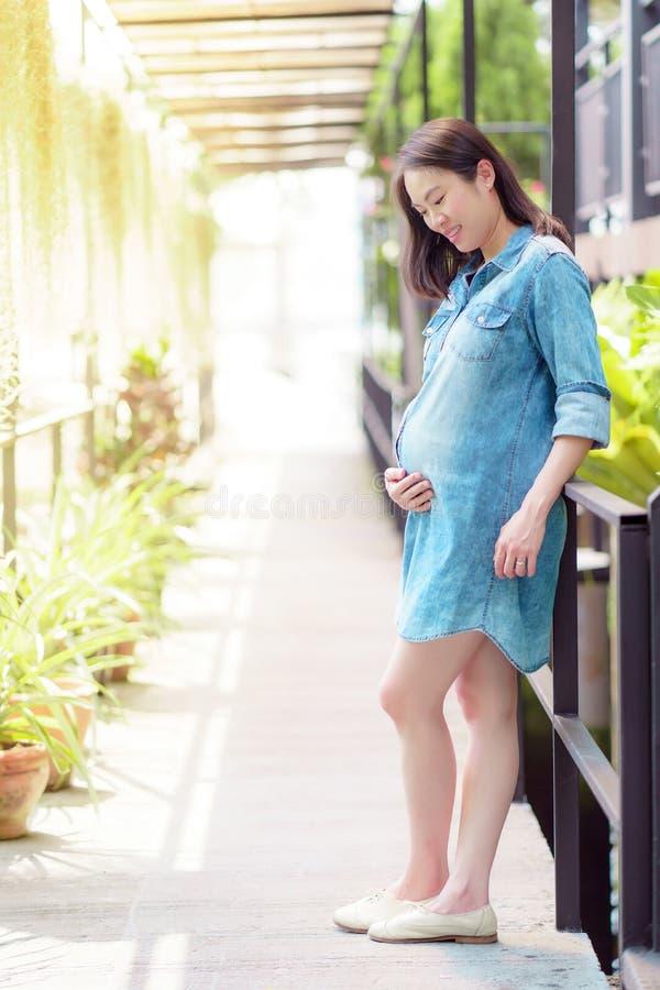 Free Pregnant Asian Woman Wearing A Denim Shirt Standing In The Garden Stock Photos - 146637453