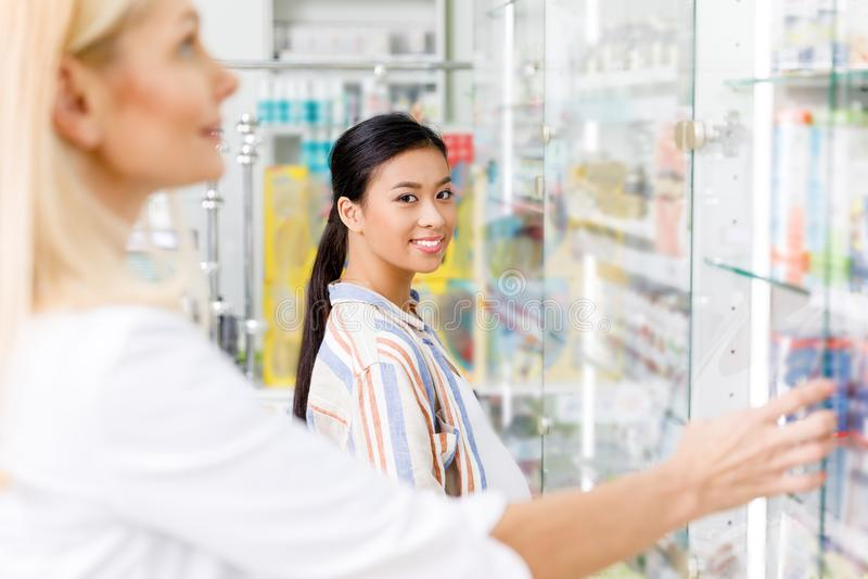 pregnant asian woman smiling at camera while pharmacist choosing medication stock image