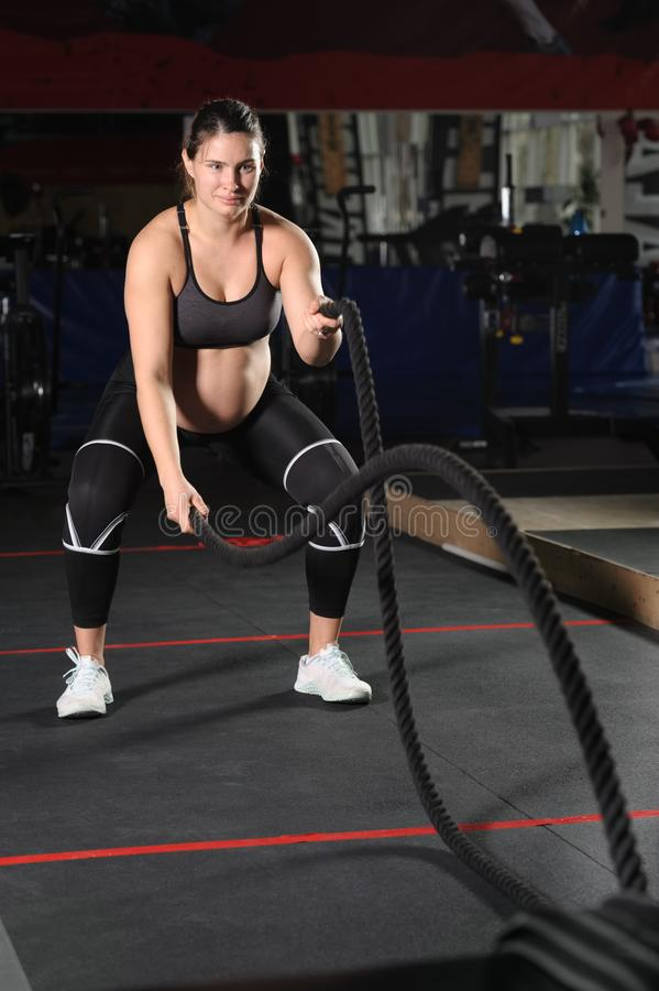 Young pregnant woman doing hard workout exercises with black ropes royalty free stock photography