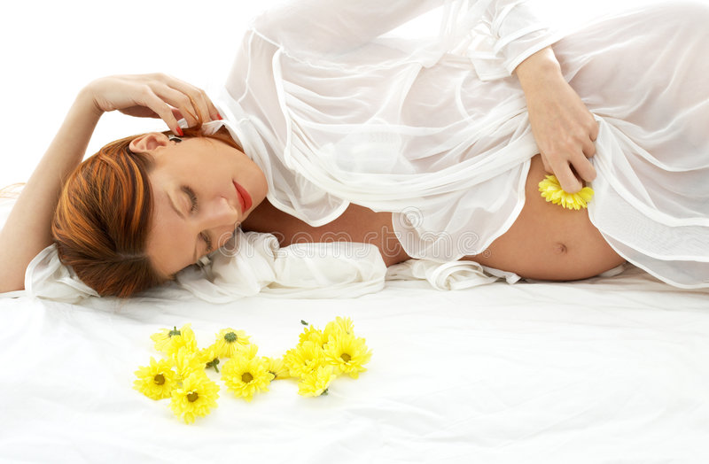 Pregnant beauty. Beautiful pregnant woman with yellow flowers in bed royalty free stock photos