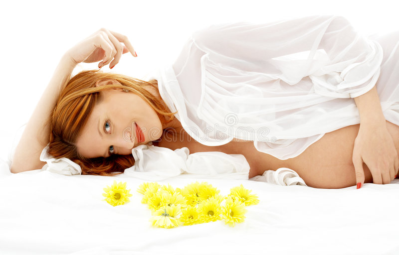 Pregnant beauty #2. Beautiful pregnant woman with yellow flowers in bed stock images