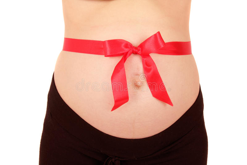 Pregnant belly with red bow. Pregnant woman belly with red bow royalty free stock image