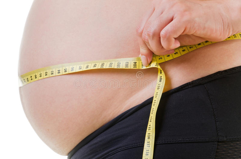 Pregnant belly. The pregnant woman measures the belly stock image