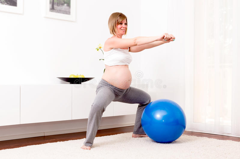 Pregnant blonde woman in her home. stock photos
