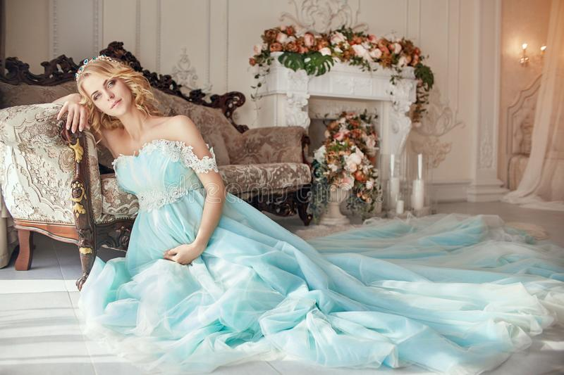 Pregnant bride blonde is preparing to become a mother and wife. Long turquoise dress on a girl body. Curly hair and a beautiful. Smile on the woman face. Two stock photography