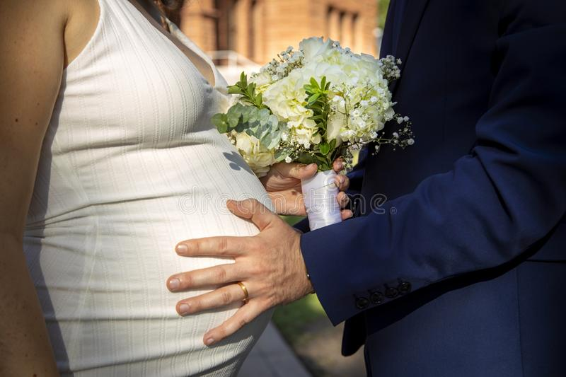 Pregnant bride with groom's hand on her belly with wedding ring stock photography