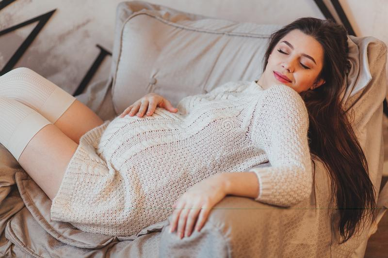 Pregnant brunette girl in a white knitted sweater lying in armchair royalty free stock images
