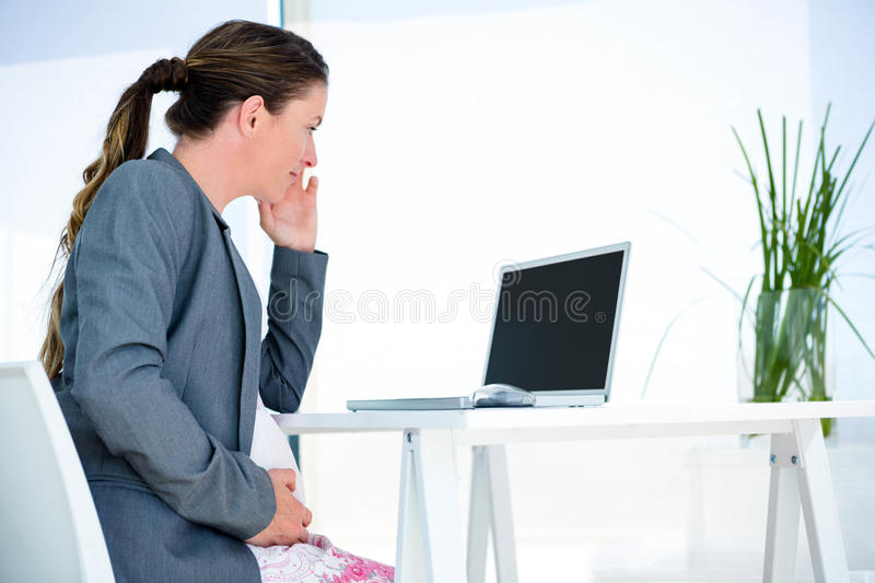 Pregnant business woman sittting at her desk. Pregnant business woman, in her office, sitting at her desk royalty free stock image