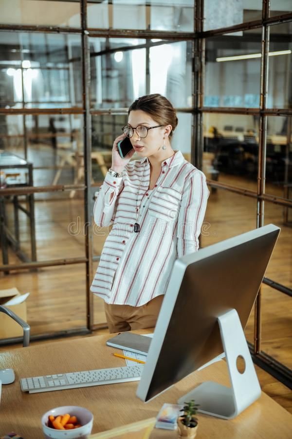 Pregnant businesswoman calling her doctor asking some questions royalty free stock image