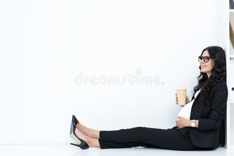 Pregnant businesswoman drinking coffee from paper cup while sitting. On floor stock photography