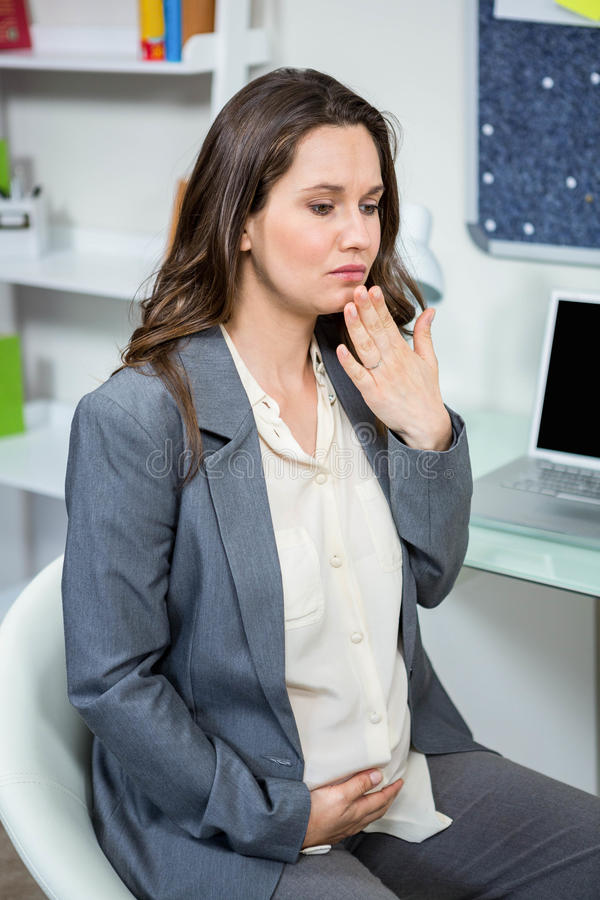 Pregnant businesswoman getting morning sickness. In home office royalty free stock image