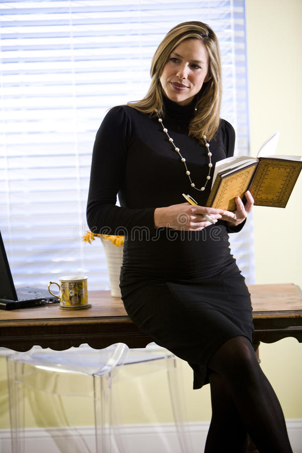Pregnant businesswoman writing notes by desk royalty free stock images
