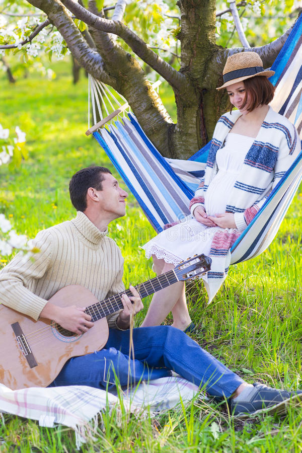 Pregnant couple in blooming garden at the picnic stock images