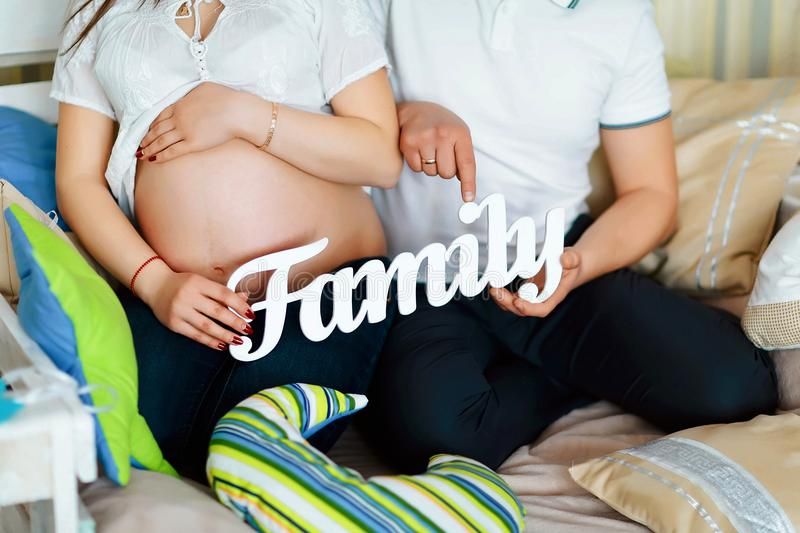 Pregnant couple with family letters, hands of a loving couple close up, the concept family royalty free stock images