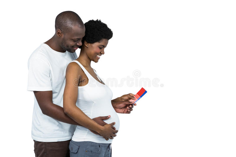 Pregnant couple holding color swatches stock photos