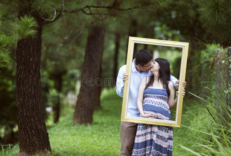 Pregnant couple kissing with frame