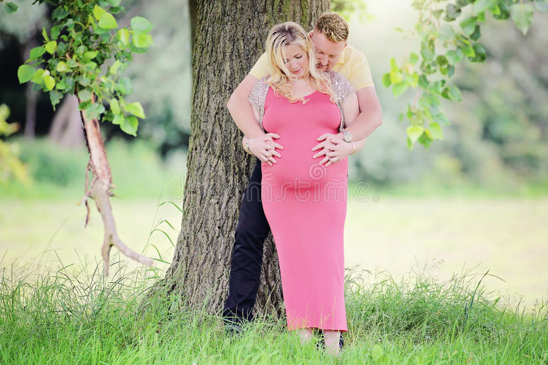 Pregnant couple natural maternity. Pregnant couple holding large belly, natural under a tree outdoors maternity concept at 34 weeks stock images