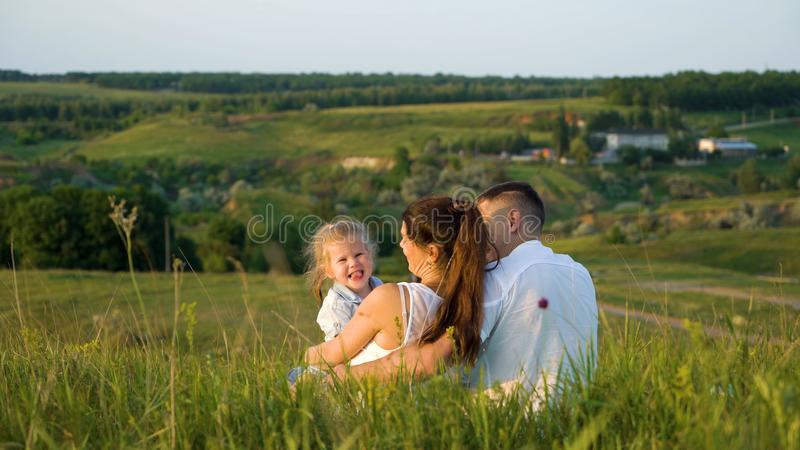 Pregnant couple with toddler daughter have leisure time outdoors back view royalty free stock photography