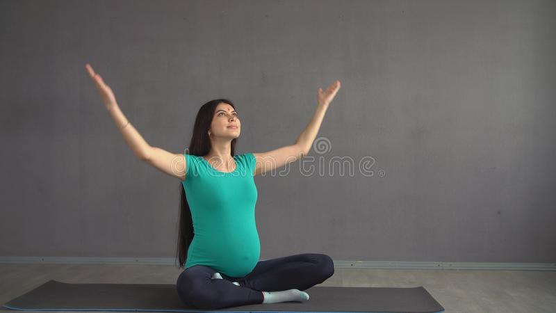 Pregnant ethnic girl engaged in yoga sitting in a lotus pose. Indian woman with hindi. stock photos