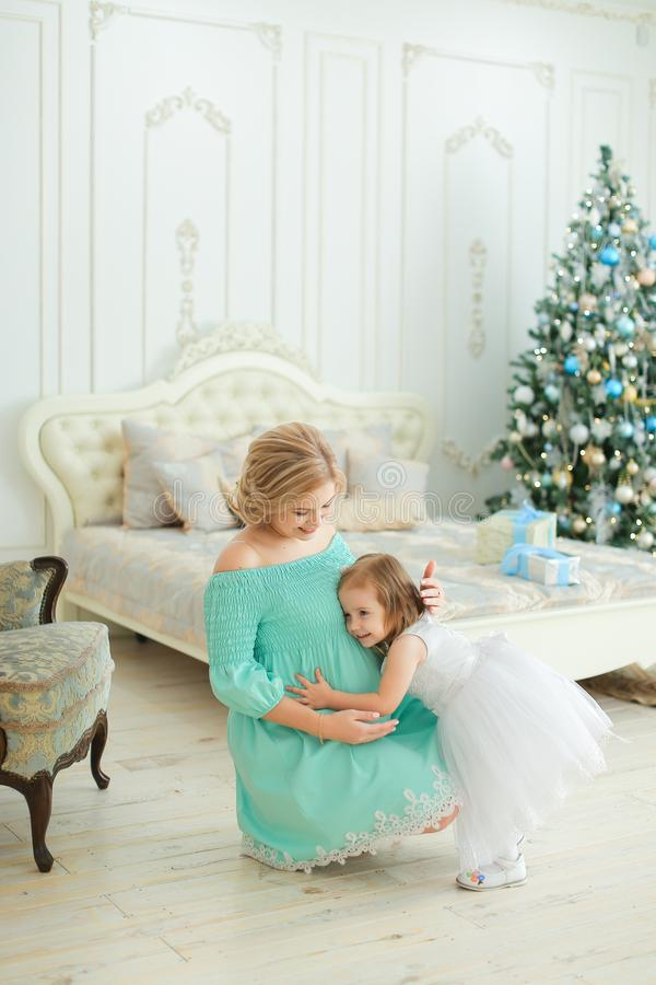 Pregnant european woman wearing blue dress hugging belly and sitting with little daughter near Christmas tree in bedroom stock images