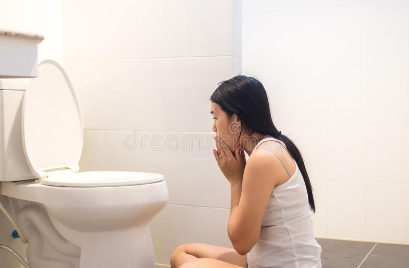 Pregnant female nausea in toilet,Asian woman with morning sickness. After wake up stock images