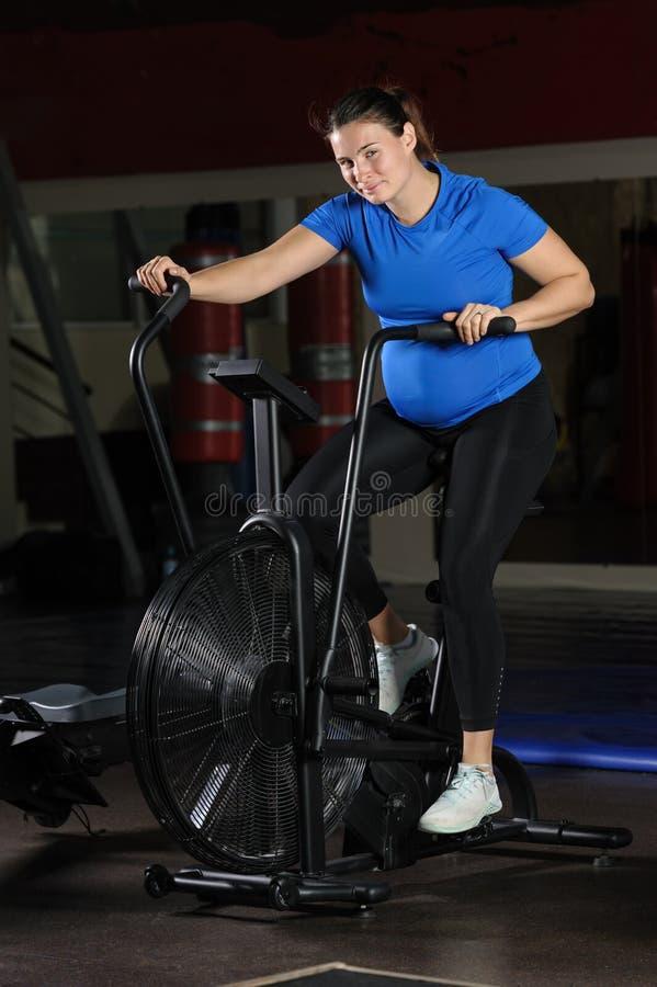 Pregnant woman doing intense workout at gym air bike stock photos