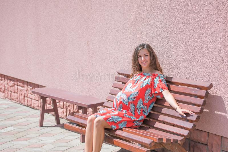 The pregnant girl basks in the sun. The concept of warm leisure - a beautiful pregnant girl with long hair, basking in a red dress stock images
