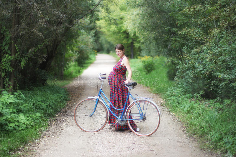 Pregnant girl with bicycle on a forest road, soft focus, side vi. Pregnant girl in plaid red dress with bicycle on a forest road, soft focus, side view stock photography