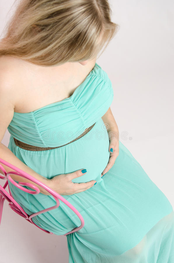 Pregnant girl on a chair. Young cute pregnant girl twenty five European-type stock photography