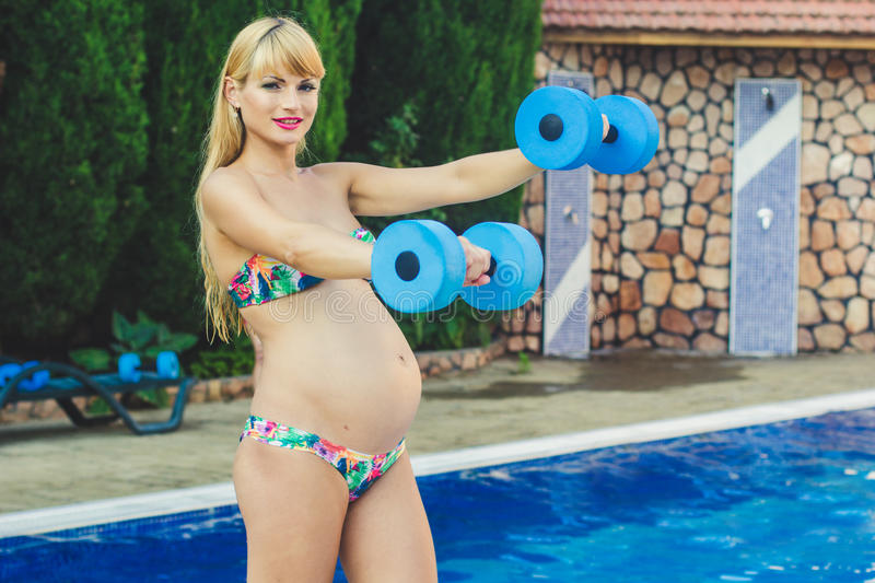 Pregnant girl with dumbbells near swimming pool stock image image 58179019 for Can you swim in a pool while pregnant