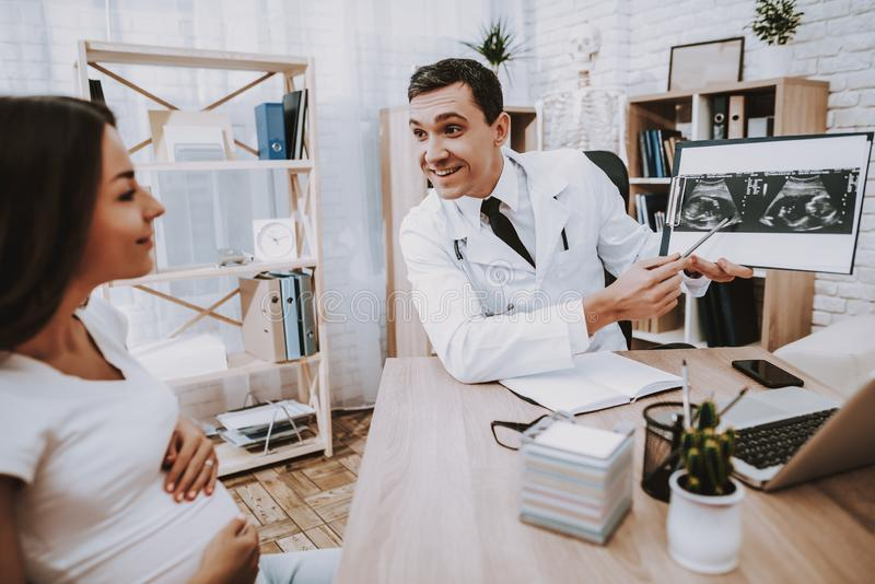 Pregnant Girl at the Gynecologist Doctor. Doctor is a Young Man. Doctor Showing the Ultrasound Results to Woman. People Sitting at Table. Persons is Smiling stock photos