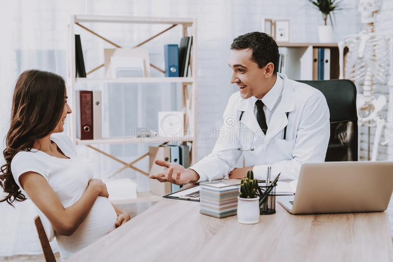 Pregnant Girl at the Gynecologist Doctor. Doctor is a Young Man. Girl is a Young Brunette Woman. People Sitting at Table and Smiling. Persons is Talking with stock images
