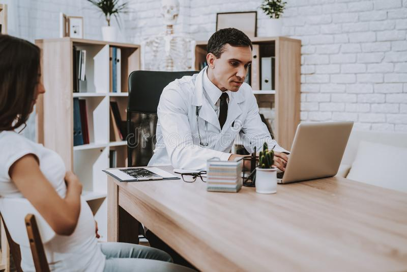 Pregnant Girl at the Gynecologist Doctor. Doctor is a Young Man. Girl is a Young Brunette Woman. Doctor is Typing Information about Woman in Laptop. People stock images