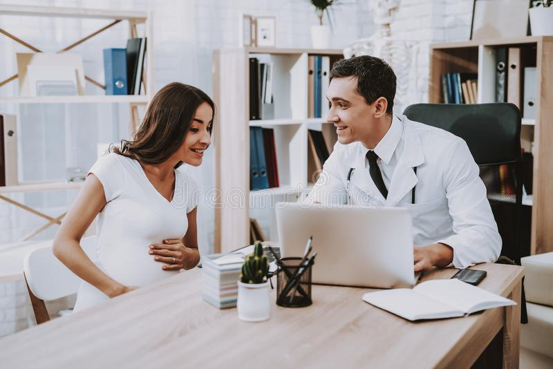 Pregnant Girl at the Gynecologist Doctor. Doctor is a Young Man. Doctor Showing Something on Laptop to Woman. People Sitting at Table. Persons is Smiling royalty free stock images