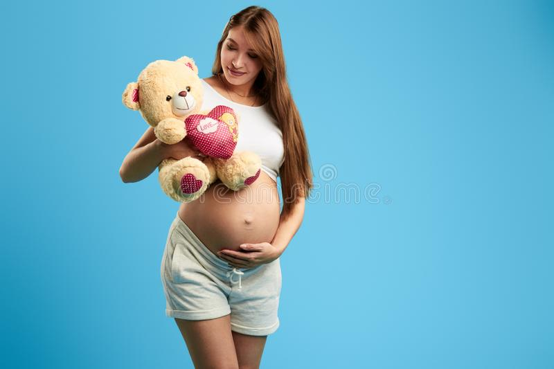 Pregnant girl having fun with tedduy bear. Pregnant childish girl having fun with tedduy bear in the studio with blue wall, copy space , close up photo stock photos